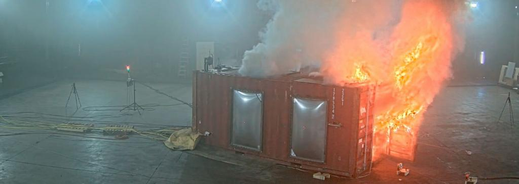 small building on fire inside of a large lab