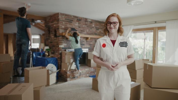 woman dressed as a smoke alarm with couple unpacking boxes in the background